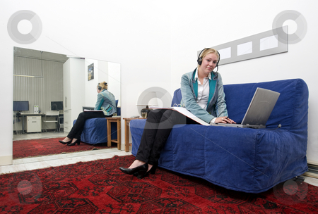Home office stock photo, Woman working on a couch on her laptop, annexed to an office space by Corepics VOF