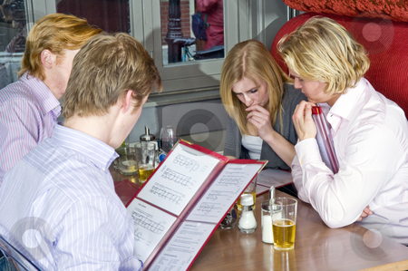 Chosing from a menu stock photo, A group of four people chosing dishes from the menu in a restaurant by Corepics VOF