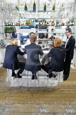 People sitting at a bar stock photo, Four customers and a barkeeper sitting, standing, talking and drinking at a bar by Corepics VOF