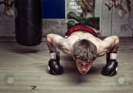 Push-ups stock photo, Muscular looking boxer doing press-ups in a graffiti clad suburban basement Focus on the dorsal muscles and biceps by Corepics VOF