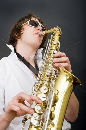 Saxophone player stock photo, A man in a white shirt and open collar passionately playing the saxophone by Corepics VOF