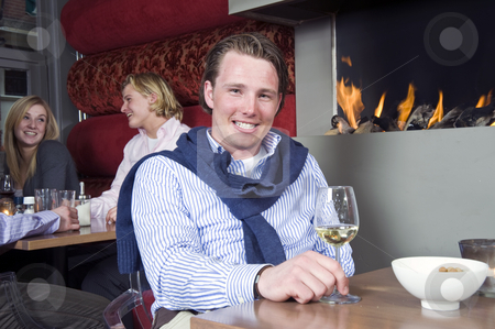 Posh Dandy stock photo, A posh looking man with his sweater around his neck and a glass of white wine in his hand sitting at a restaurant table in front of the fireplace by Corepics VOF