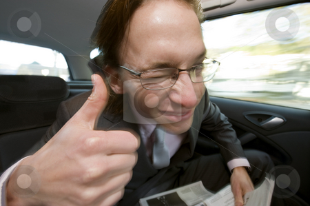 Happy backseat passenger stock photo, The happy businessman in the backseat leaning forward giving a thumbs-up while winking. Motion blur with fill flash on the rear curtain. by Corepics VOF