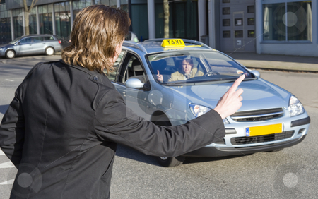 Hauling a taxi stock photo, A businessman raising his hand to haul a passing taxi. The driver acknowledges, but speeds on. Slight motion blur in the taxi by Corepics VOF