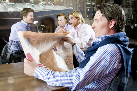 Reading a newspaper stock photo, A young male reading his newspaper in a restaurant with other customers discussing on the background by Corepics VOF