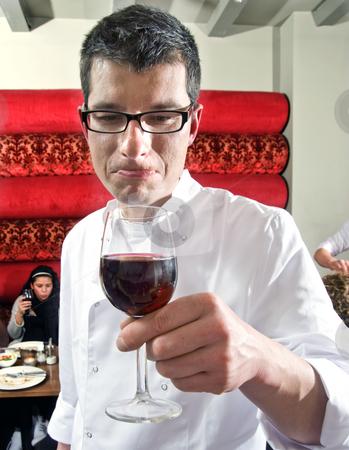 Wine waiter savouring wine stock photo, Wine waiter savouring wine in a restaurant witch customers on the background by Corepics VOF