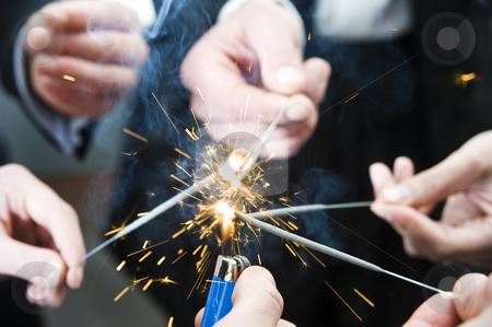 Igniting spark sticks stock photo, Lighter flame igniting spark sticks on new years evening by Corepics VOF