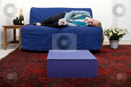 Relaxing stock photo, Tired, barely awake woman relaxing on a couch holding a remote control in her hand by Corepics VOF
