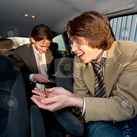 Tipping the Cabby stock photo, A customer in the backseat giving a tip to the cabby after having reached the destination by Corepics VOF