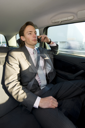 Backseat business call stock photo, A young businessman making a call in the backseat of a taxi by Corepics VOF