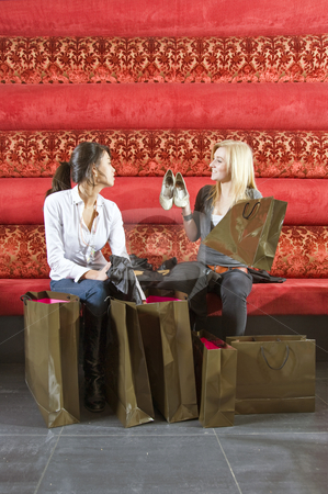 Showing purchases stock photo, Two young women showing their recent purchases to one another by Corepics VOF