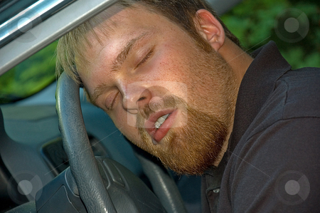 Man Asleep In a Car At The Wheel stock photo, This young Caucasian man is asleep at the wheel of a car, with some drool beginning to run out of his mouth. by Valerie Garner