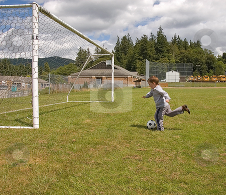 Little Boy in Cowboy Boots Kicking Soccer Ball stock photo, This little boy wearing cowboy boots is midway to kicking a soccer ball into a net. by Valerie Garner