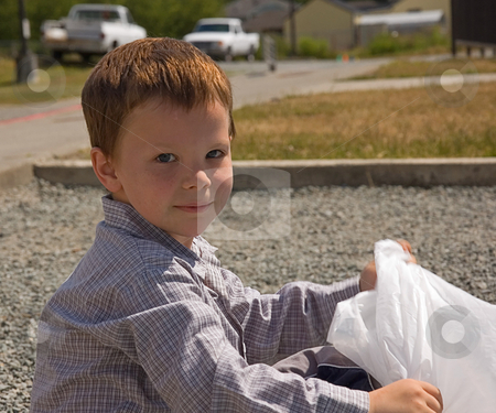 Little Boy with Garbage Bag Outside stock photo, This 5 year old Caucasian boy is sitting outside with a white garbage bag. by Valerie Garner