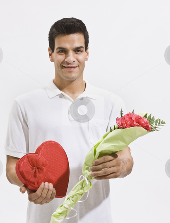 Happy Man Holding Candy and Flowers stock photo, A happy looking man holding flowers and candy. Vertically framed shot. by Jonathan Ross