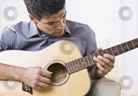 Attractive Man Playing Guitar stock photo, An attractive man playing an acoustic guitar.  Horizontally framed shot. by Jonathan Ross