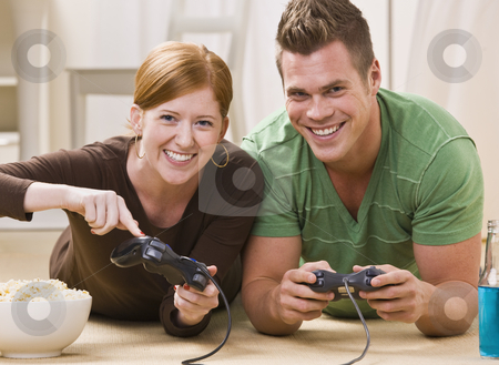 Happy Young Couple Playing Video Games stock photo, A happy young couple smiling and playing video games together in their home. Horizontally framed shot. by Jonathan Ross