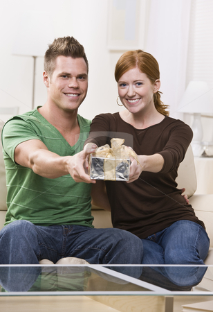 Happy Young Couple with Present stock photo, An attractive and young caucasian holding out a present and smiling.  They are seated on a couch in a living room and are looking directly at the camera. Vertically framed shot. by Jonathan Ross