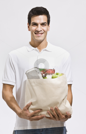 Attractive Man Holding Groceries stock photo, Attractive hispanic man holding a bag of groceries and smiling at the camera. Vertically framed shot. by Jonathan Ross