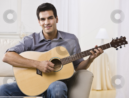 Relaxed Man Playing Guitar stock photo, An attractive and relaxed looking man sitting on a couch and playing the guitar.  He is smiling at the camera. Horizontally framed shot. by Jonathan Ross