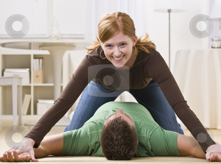 Playful Redhead Pinning Man stock photo, A playful young woman pinning a man to the floor. She is smiling directly at the camera.  Horizontally framed shot. by Jonathan Ross
