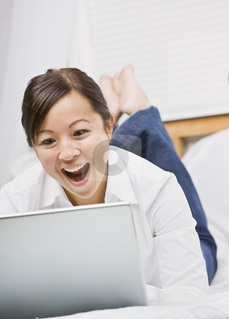 Cute Asian Woman Using Laptop stock photo, A cute young asian woman smiling excitedly at her laptop screen.  She is relaxing in bed. Vertically framed shot. by Jonathan Ross