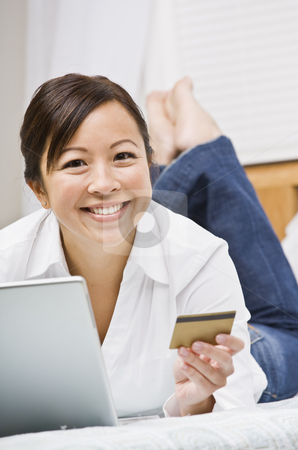 Beautiful Asian Woman with Credit Card stock photo, Beautiful asian woman holding a credit card and using a laptop.  She is smiling at the camera.  Vertically framed shot. by Jonathan Ross