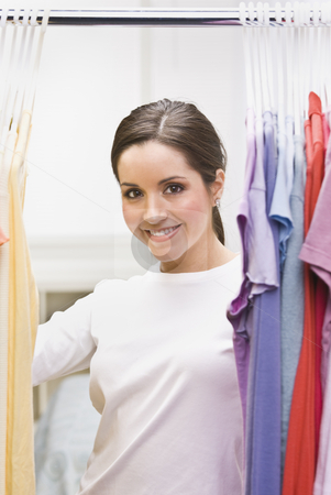 Beautiful Brunette in Closet stock photo, A beautiful brunette looking through clothing in a closet.  She is smiling at the camera. Vertically framed shot. by Jonathan Ross