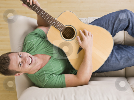 Attractive Man Playing Guitar stock photo, An above view of an attractive young man lying on the couch and playing a guitar.  He is smiling directly at the camera.  Horizontally framed shot. by Jonathan Ross