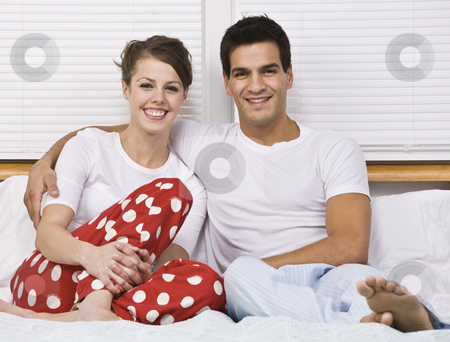 Smiling Couple Sitting in Bed stock photo, An attractive couple smiling and sitting in bed together.  Horizontally framed shot. by Jonathan Ross