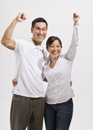 Attractive Asian Couple Cheering stock photo, An attractive young asian couple cheering with their fists in the air.  They are smiling at the camera.  Vertically framed shot. by Jonathan Ross