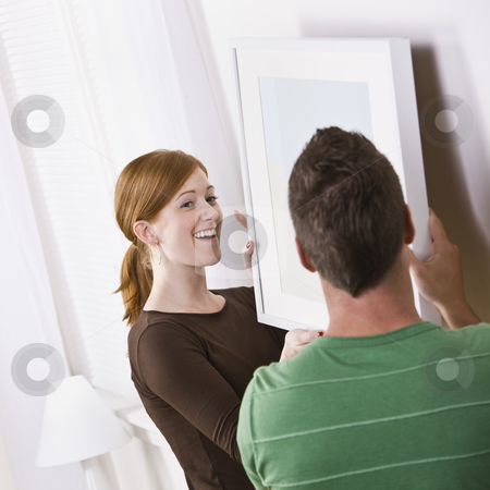 Happy Young Couple Hanging Frame stock photo, An attractive young couple hanging a picture frame in their home. Square composition. by Jonathan Ross