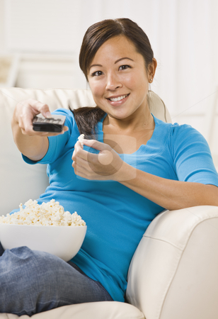 Beautiful Asian Woman Watching T.V. stock photo, A beautiful young asian woman sitting on a couch. She is holding a bowl of popcorn and is using a remote. She is smiling directly at the camera. Vertically framed shot. by Jonathan Ross