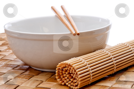 A horizontal image of a pair of chopsticks on a white bowl with  stock photo, A horizontal image of a pair of chopsticks on a white bowl with a suhi rolling mat on a weaved placemat by Vince Clements