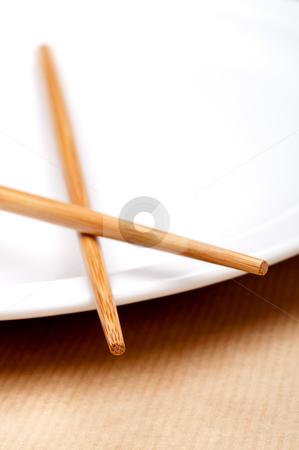 A vertical macro of a pair of chopsticks on a white plate stock photo, A vertical macro of a pair of chopsticks on a white plate by Vince Clements