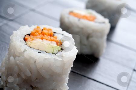 A tilted shallow focus horizontal macro of 3 rolls of sushi stock photo, A tilted shallow focus horizontal macro of 3 rolls of sushi by Vince Clements