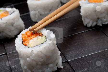 A tilted horizontal shallow focus macro of sushi with copsticks  stock photo, A tilted horizontal shallow focus macro of sushi with copsticks on a black wooden background by Vince Clements