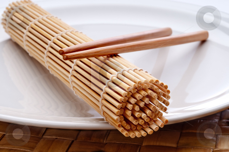 A horizontal macro of a pair of chopsticks and a sushi rolling m stock photo, A horizontal macro of a pair of chopsticks and a sushi rolling mat on a white plate by Vince Clements