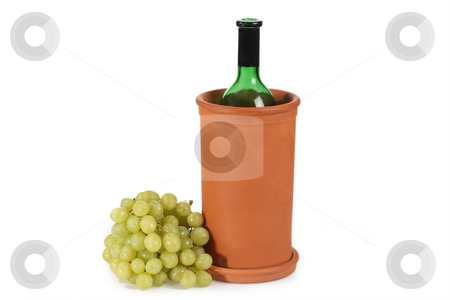 Wine cooler stock photo, Opened green wine bottle with grapes in traditional terracotta wine cooler. by Birgit Reitz-Hofmann