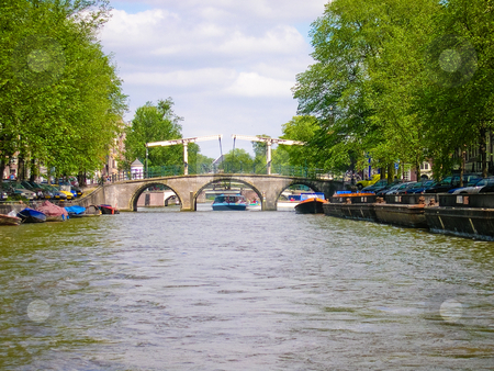 Amsterdam canal stock photo, Boat going under a bridge on an Amsterdam canal by Jaime Pharr