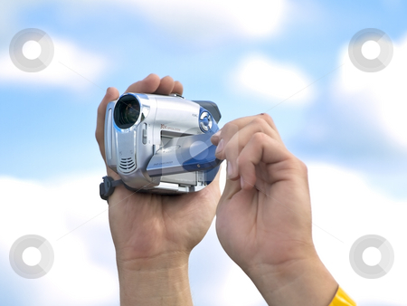 Videocamera stock photo, Man hands hold camera against cloudy sky by Sergej Razvodovskij