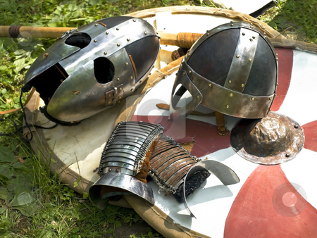 Armor stock photo, Knight metal helmets over the stripped shield by Sergej Razvodovskij
