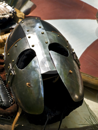 Helmet stock photo, Knight metal helmet over the stripped shield by Sergej Razvodovskij