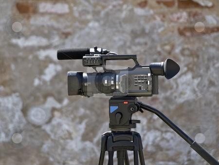Videocamera stock photo, Single working videocamera against the old wall by Sergej Razvodovskij