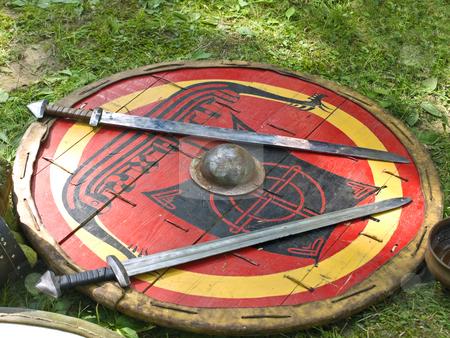 Swords on shield stock photo, Two swords on the red painted shield by Sergej Razvodovskij