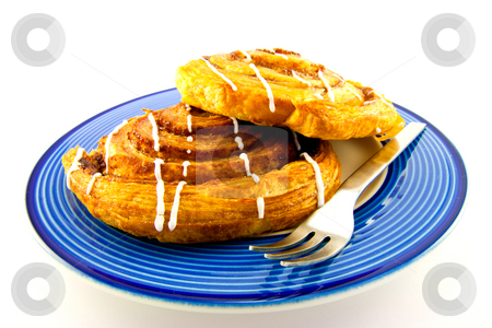 Cinnamon Buns on a Blue and White Plate stock photo, Two cinnamon buns with a fork on a blue and white plate with clipping path on a white background by Keith Wilson