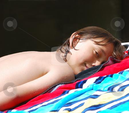 Teen Sunbathing stock photo, Teen boy lying down on a beach towel and sunbathing. by Denis Radovanovic