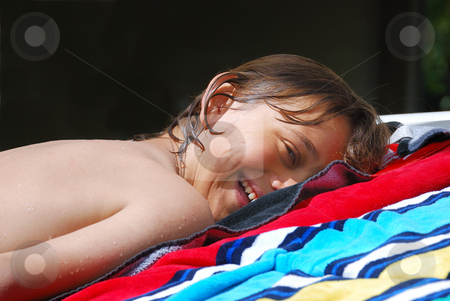 Smiling Teen Boy Sunbathing stock photo, Smiling teen boy lying down on a beach towel and sunbathing. by Denis Radovanovic