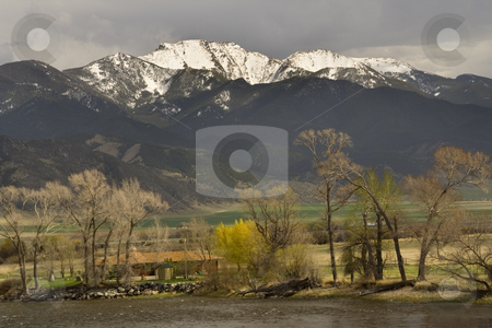 Small Farm by River in front of Snow Mountains  stock photo, Small Farm in front of Snow Covered Mountains Outside Butte, Montana--Big Sky Country by William Perry