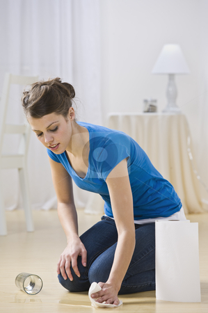 Young Woman Cleaning Water Spill stock photo, An attractive young woman cleaning up a spilled glass of water in her home.  She is using paper towels and is cleaning a hardwood floor. Vertically framed shot. by Jonathan Ross